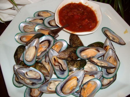 Steamed mussels, served in shells and with tomato sauce in a round plate 스톡 콘텐츠