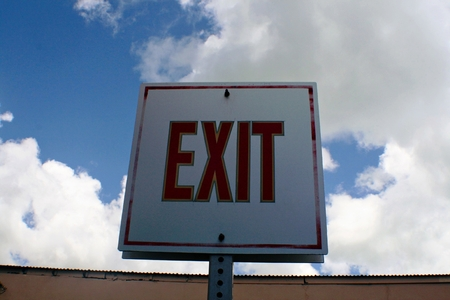 Exit sign in white board with clouds and skies background