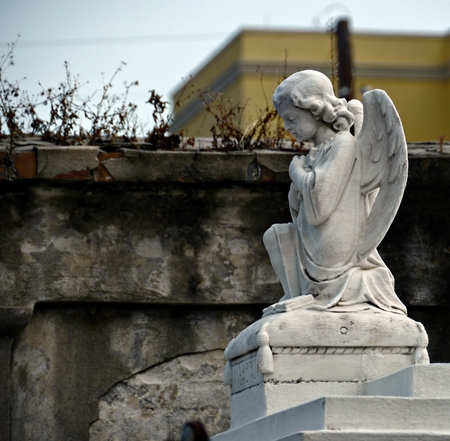 A statue of a small angel on top of a tomb at a cemetery