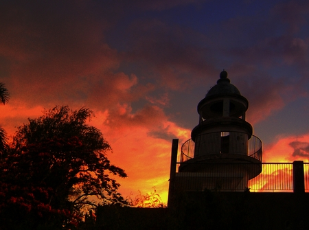 An old Japanese lighthouse at Navy Hill, Saipan silhouetted against a fiery sunset