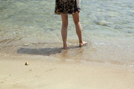 Legs of an unrecognizable woman wading in the clear waters of a tropical beach