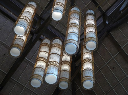 Artistic chandelier tubes of light covered with native decoration hanging from the ceiling