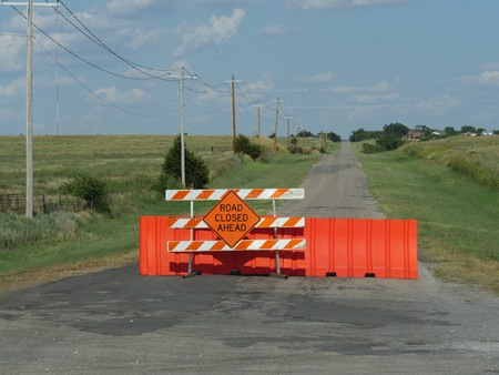 Road Closed Ahead sign in a blocked paved road