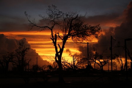 Fiery sunset amid the chaos and devastation left by a typhoon in a tropical island