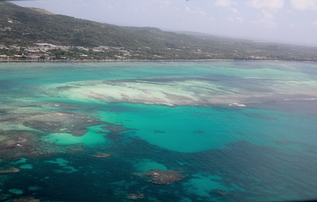 Saipan lagoon aerial view with its different shades of blue and green waters and the Beach Road in the distance