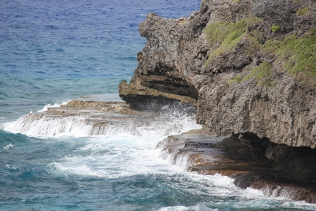 Waves slapping against rock platforms and sharp cliffs in the ocean
