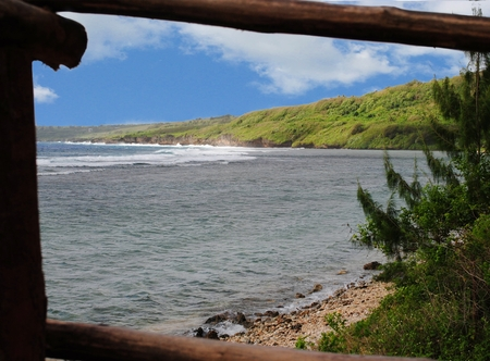 A bamboo window serves as a natural frame for this scenic beachside view in Laulau Beach, Saipan