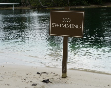 No Swimming sign posted on the white sand beside a lake Stock fotó