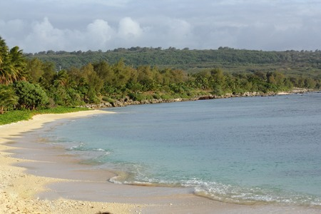 Beautiful sloping beach with white sands and gentle waves in a tropical island 写真素材