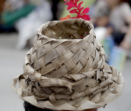 Native handmade hat of woven coconut leaves at a tropical island, with a bird of paradise flower on top
