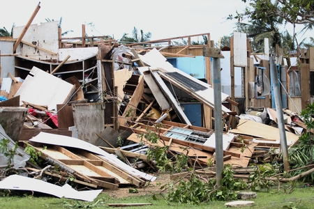 The damaged remains of wooden houses after a typhoon hit a tropical island, with missing roofs and devastation all around Stockfoto