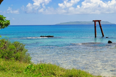 Beautiful seascape with an old relic from a shipwreck protruding in the crystal clear waters, with the Goat Island seen in the distance.