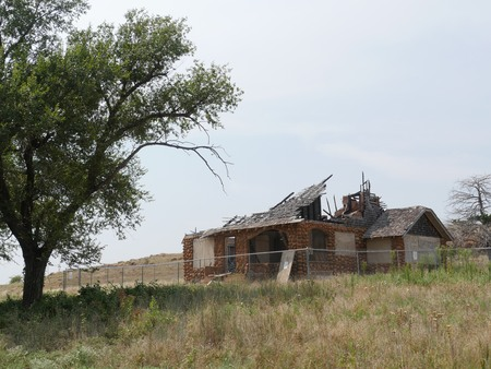 Abandoned brick and wooden building in a fenced area with a tree on one side