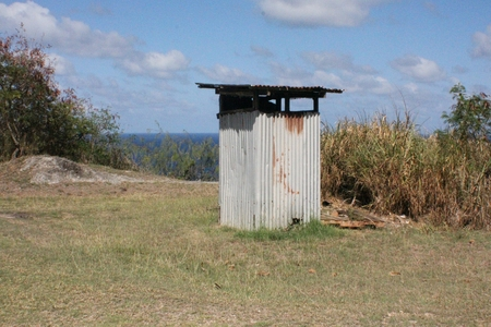 An outhouse made of rusting tin roof in the jungle beside the bushes Фото со стока
