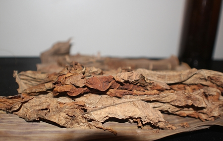 pile of dried tobacco leaves spread out on a table