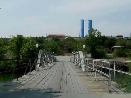 Old wooden bridge, with water tanks in the distance at the Comanche County, Oklahoma 写真素材