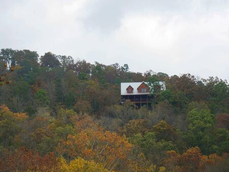 Log cabin seen through the colorful foliage in the forest on a beautiful autumn day Stockfoto