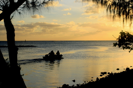 Silhouette of three men out on a boat to go fishing at sunset in Saipan, Northern Mariana Islands 免版税图像