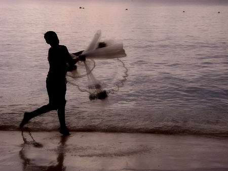 An unrecognizable fisherman is silhouetted throwing out a fishing net at the seaside at twilight.