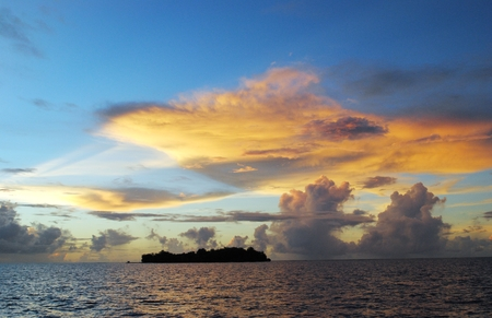 Magical play of clouds in the skies at sunset reflected in the waters of Saipan lagoon, with Managaha Island in view