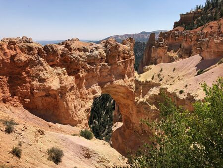 Wide shot of the Natural Bridge, an 85-foot arch carved out of sedimentary red rock at Bryce Canyon National Park in Utah. Stock Photo