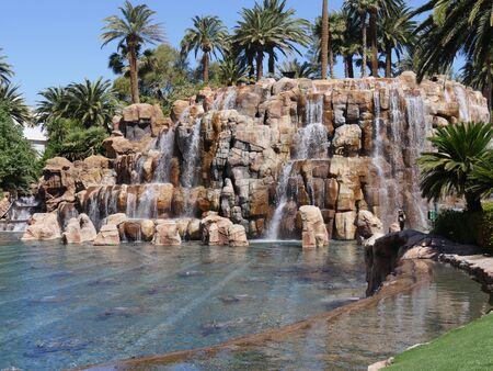 Waterfalls flowing into a pond at a landscaped garden Imagens