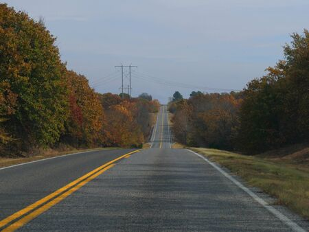 Stretch of  paved road with the colors of autumn in the trees Banco de Imagens
