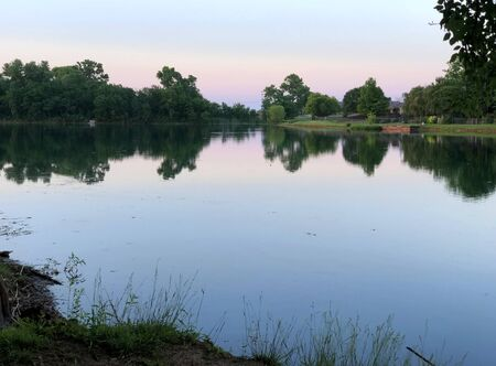 Wide view of the lake with trees reflected in the waters Banco de Imagens