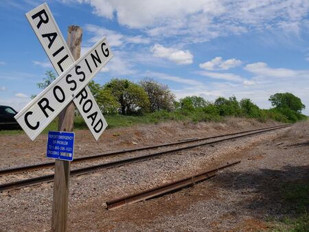 Medium wide shot of a crossing sign at a railroad track Stock Photo - 128299116