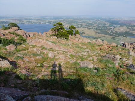 Wide view from the peak of Mt. Scott, Oklahoma, USA, with the shadows of a man and woman from the overlook. 免版税图像