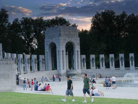 Washington, D.C., USA-September 2017: Visitors linger around the water fountains at the National World War 11 Memorial at sunset in Washington, District of Columbia. 新聞圖片