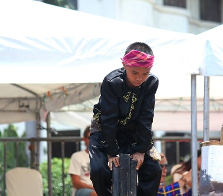 Davao City, Philippines-August 2014: A performer props himself up on poles at the Kadawayan festival for the streetdancing competition.  Kadayawan is celebrated August each year to give thanks for life and an abundant harvest.