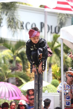 Davao City, Philippines-August 2014: A boy balances himself on bamboos poles during a performance at  the streetdancing competition. Kadayawan is celebrated August each year to give thanks for life and an abundant harvest.