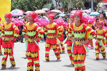 Davao City, Philippines-August 2014: Streetdancing competition participants in colorful costumes and lively performance. Kadayawan is celebrated August each year to give thanks for life and an abundant harvest.
