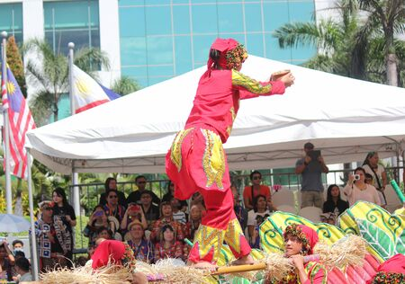 Davao City, Philippines-August 2014: A girl in colorful costume balances herself on top of bamboo poles at the streetdancing competition. Kadayawan is celebrated August each year to give thanks for life and an abundant harvest.