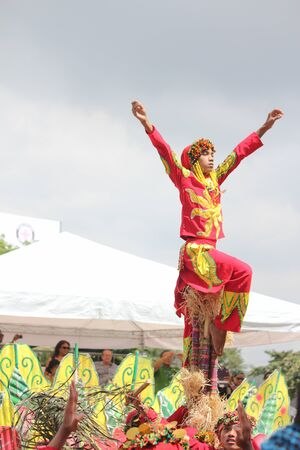 Davao City, Philippines-August 2014: Portrait view of a performer in colorful costume with arms raised balancing himself on top of bamboo poles at the streetdancing competition.