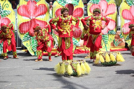 Davao City, Philippines-August 2014: Wide shot of participants in colorful costumes dancing in the streets. Kadayawan is celebrated August each year to give thanks for life and an abundant harvest.
