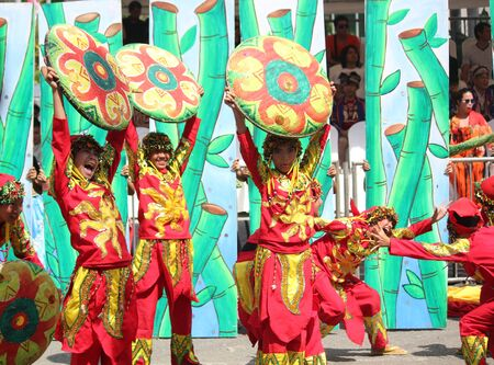 Davao City, Philippines-August 2014: Street dancers in colorful costumes and props perform a lively number in the streets. Kadayawan is celebrated August each year to give thanks for life and an abundant harvest.