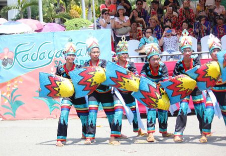 Davao City, Philippines-August 2014: Streetdancing competition participants do a lively performers as crowds in tribal costumes watch from the sidelines. Kadayawan is celebrated August each year to give thanks for life and an abundant harvest.