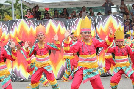 Davao City, Philippines-August 2014: Lively performance of street dancers at the Kadayawan festival with crowds watching from the sidelines. Kadayawan is celebrated August each year to give thanks for life and an abundant harvest.