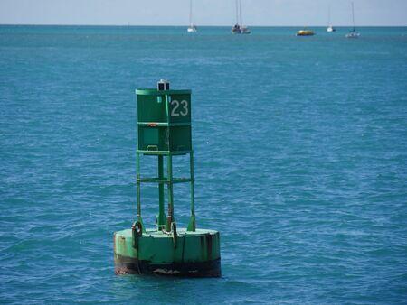 Une bouée flotte dans l'océan à quelques mètres de la jetée