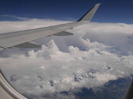 Stormwolken gezien vanuit een vliegtuigraam, met een vliegtuigvleugel in zicht. Stockfoto