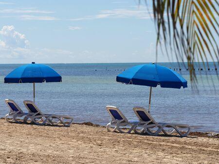 Blue loungers and umbrella at Hicks Beach along S. Roosevelt Boulevard, Key West, Florida.