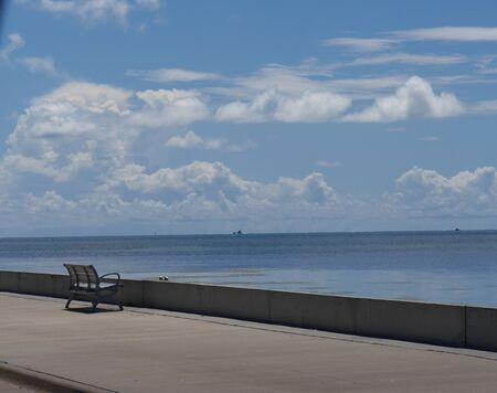 Wide shot with a bench facing the ocean along S Roosevelt Boulevard, Key West, Florida. 免版税图像