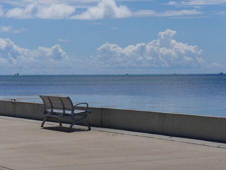 Medium wide shot of a bench facing the ocean along S Roosevelt Boulevard, Key West, Florida.