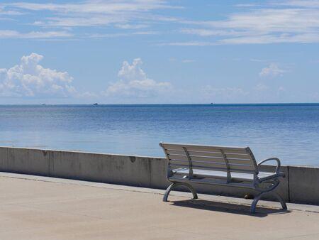 Medium close up of a bench facing the ocean along S Roosevelt Boulevard, Key West, Florida. Фото со стока
