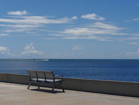 Beautiful view of the ocean with a bench facing the waters along S Roosevelt Boulevard, Key West, Florida.