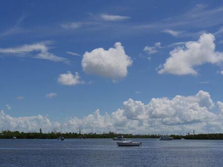 Boats in the bay along the coast of Key West, Florida, with gorgeous clouds in the skies.