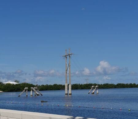 Power poles in the water near a dock at Key West, Florida
