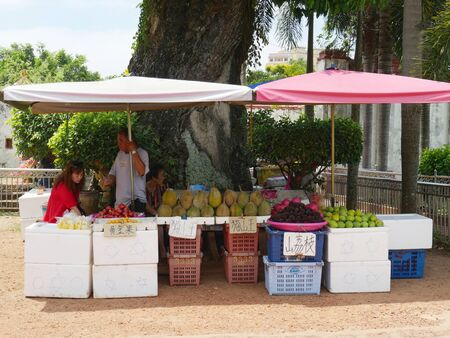 Malacca, Malaysia--Febuary 2018:  Vendors sell assorted fruits like durian, mango and others outside the Poh San Teng Temple in Malacca, Malaysia.